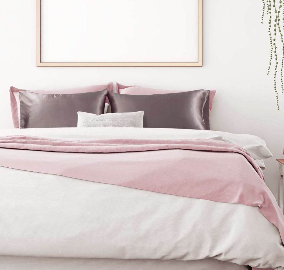 gray satin pillows on a bed