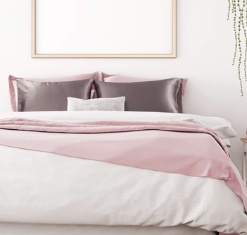 The gray satin cases on pillows on a bed