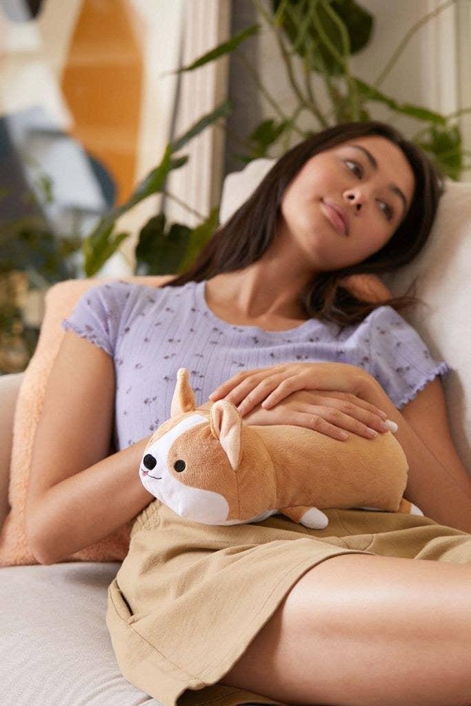 Model holding a plush corgi on their pelvis area.