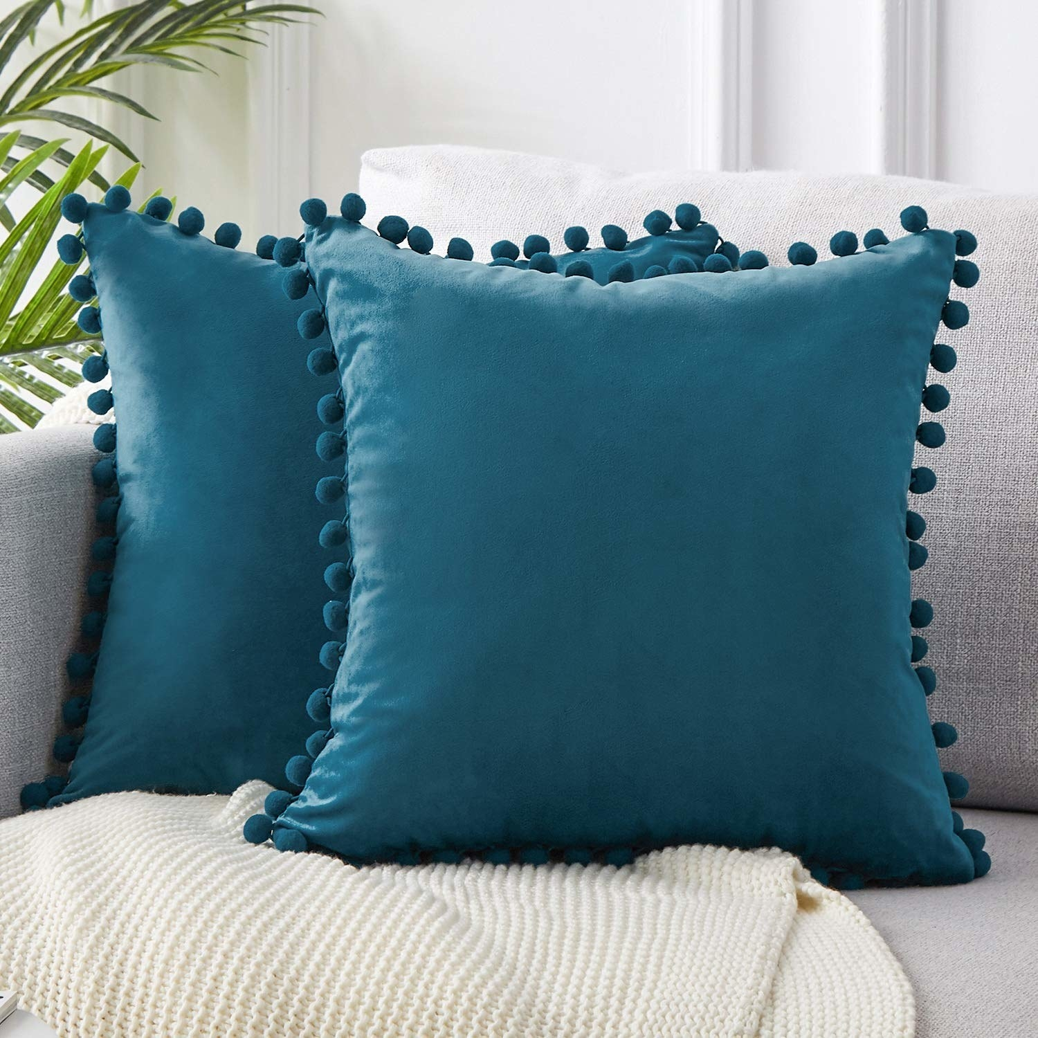 The velvet pillow covers in teal with decorative pom-poms