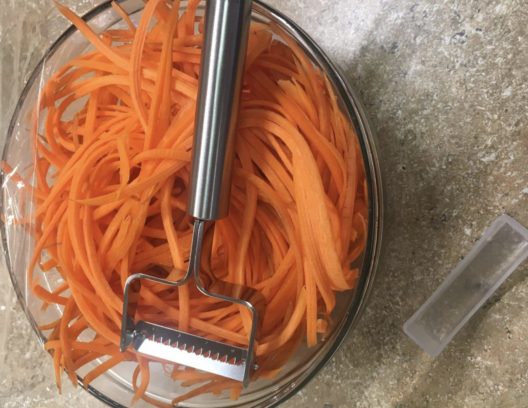 A reviewer photo of the peeler and a bowl of shredded carrots