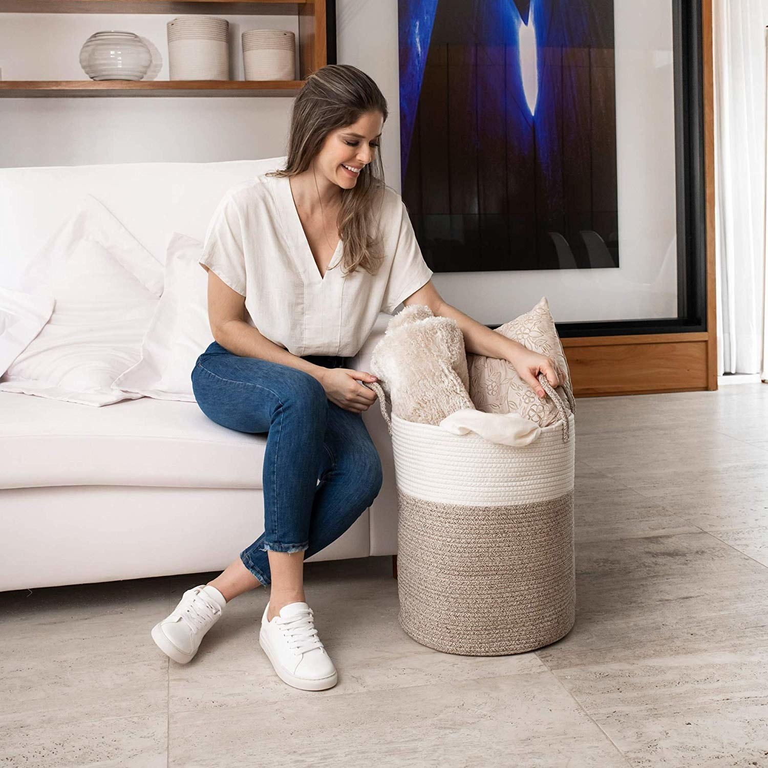 Model posing with two tone braided beige and ivory laundry hamper with side handles