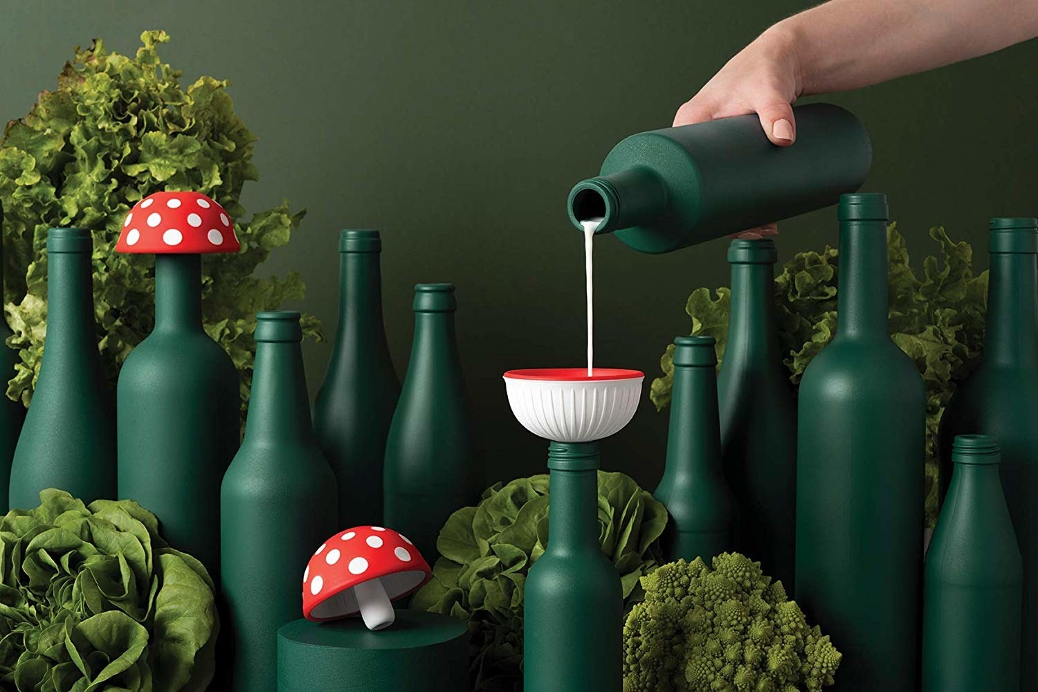 hand pouring a liquid from one bottle to another through the bowl-shaped mushroom funnel