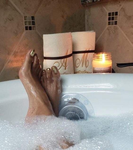 A reviewer's feet resting on the drain cover with their bubble bath reaching almost the top of the tub