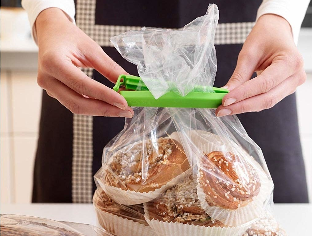 A person putting the clip on bread and pastries.