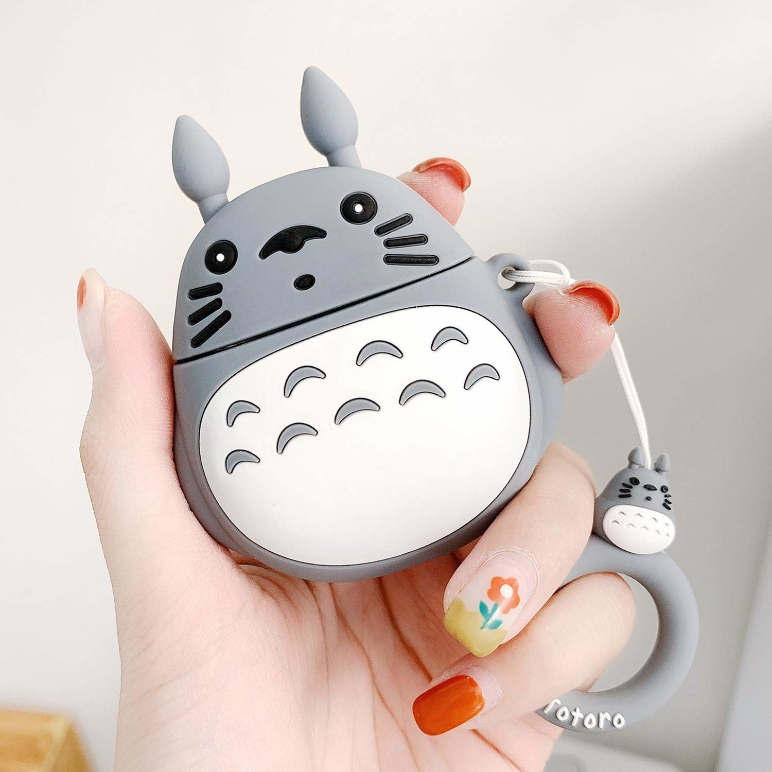 "Hand holding the Totoro shaped case with a ring handle attachment with another small Totoro on it and the text ""Totoro"""