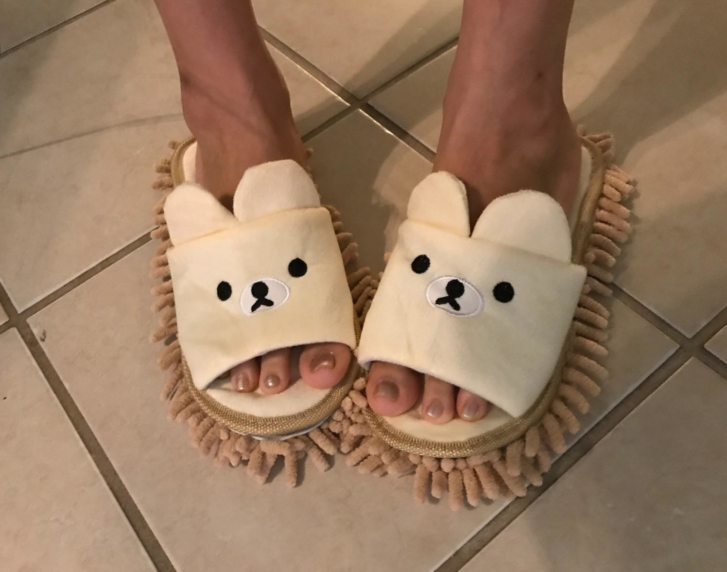Reviewer wearing the slippers in beige with a face and ears on the top and light brown mop on the bottom.