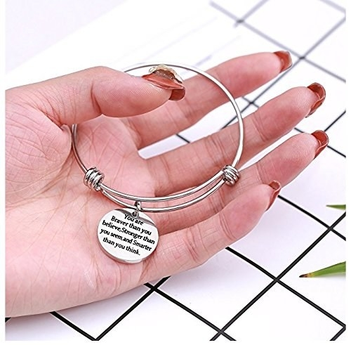 """A stainless steel bracelet with a charm that reads, """"You are braver than you believe, stronger than you seem, and smarter than you think""""."""