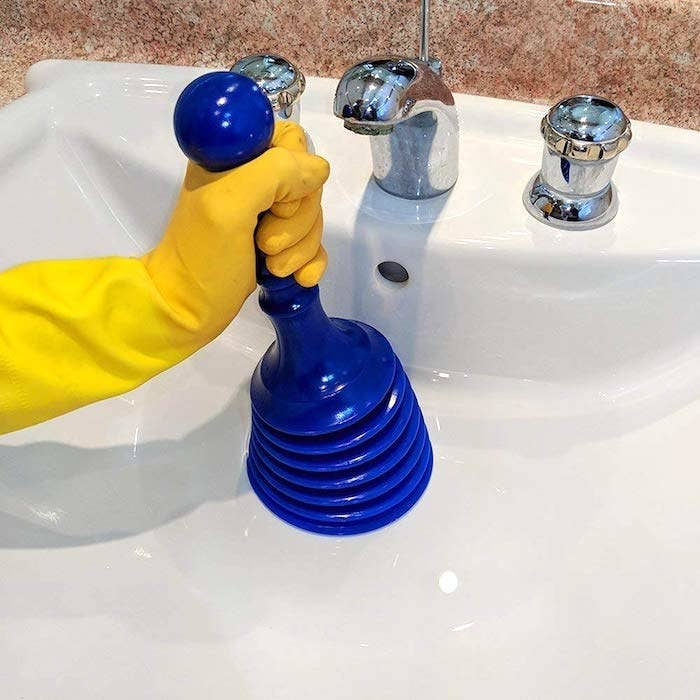 reviewer's hand holding a mini plunger inside a sink