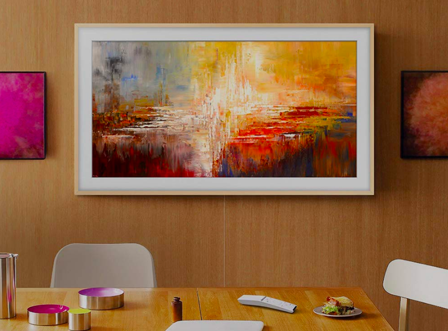 The television hung up in a dining room, displaying abstract art to blend in with the framed art pieces beside it