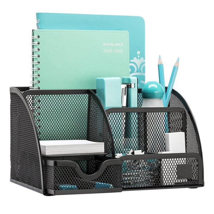 The desktop organiser in black with multiple stationery items placed in it.