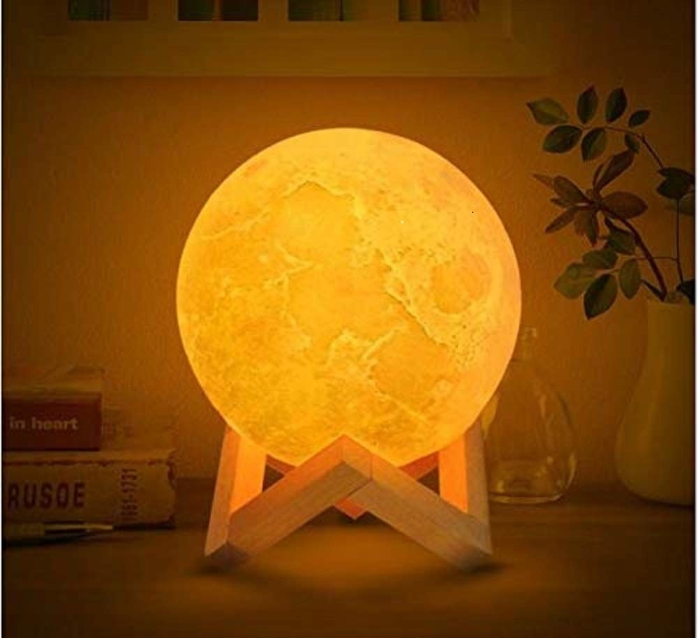 A moon-shaped lamp with a wooden stand on a table, turned on with yellow light