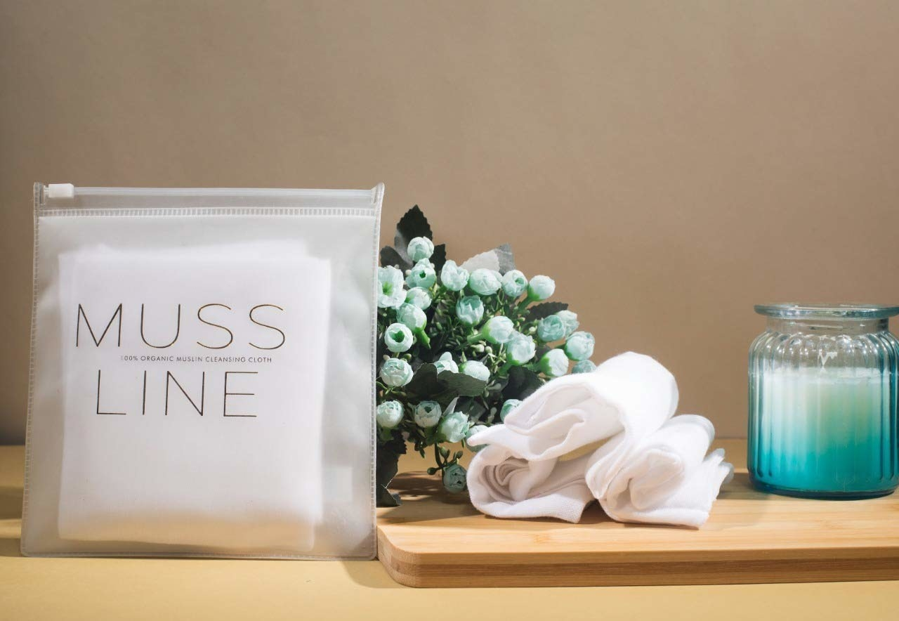 A closed pouch of muslin makeup remover pads on a table next to some used pads