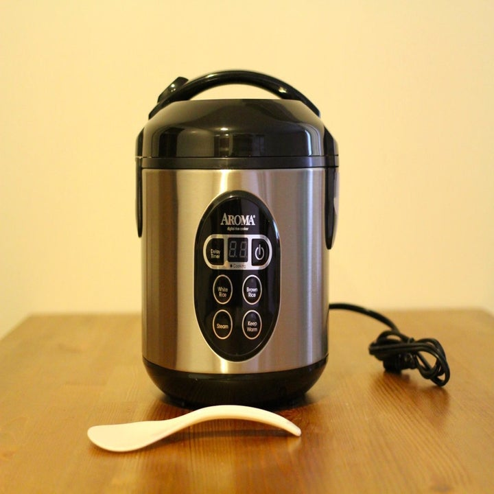 The stainless steel rice cooker showing buttons for several modes of cooking