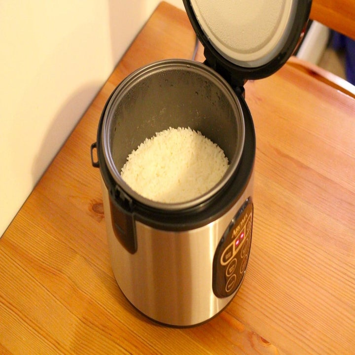 The rice cooker with its lid off to show rice cooking inside