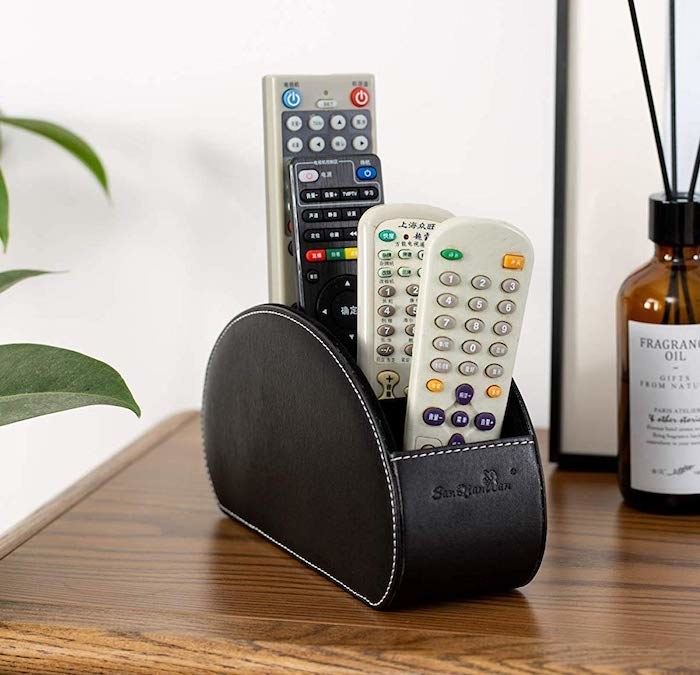 An oval-shaped container with four remote controllers standing up inside it