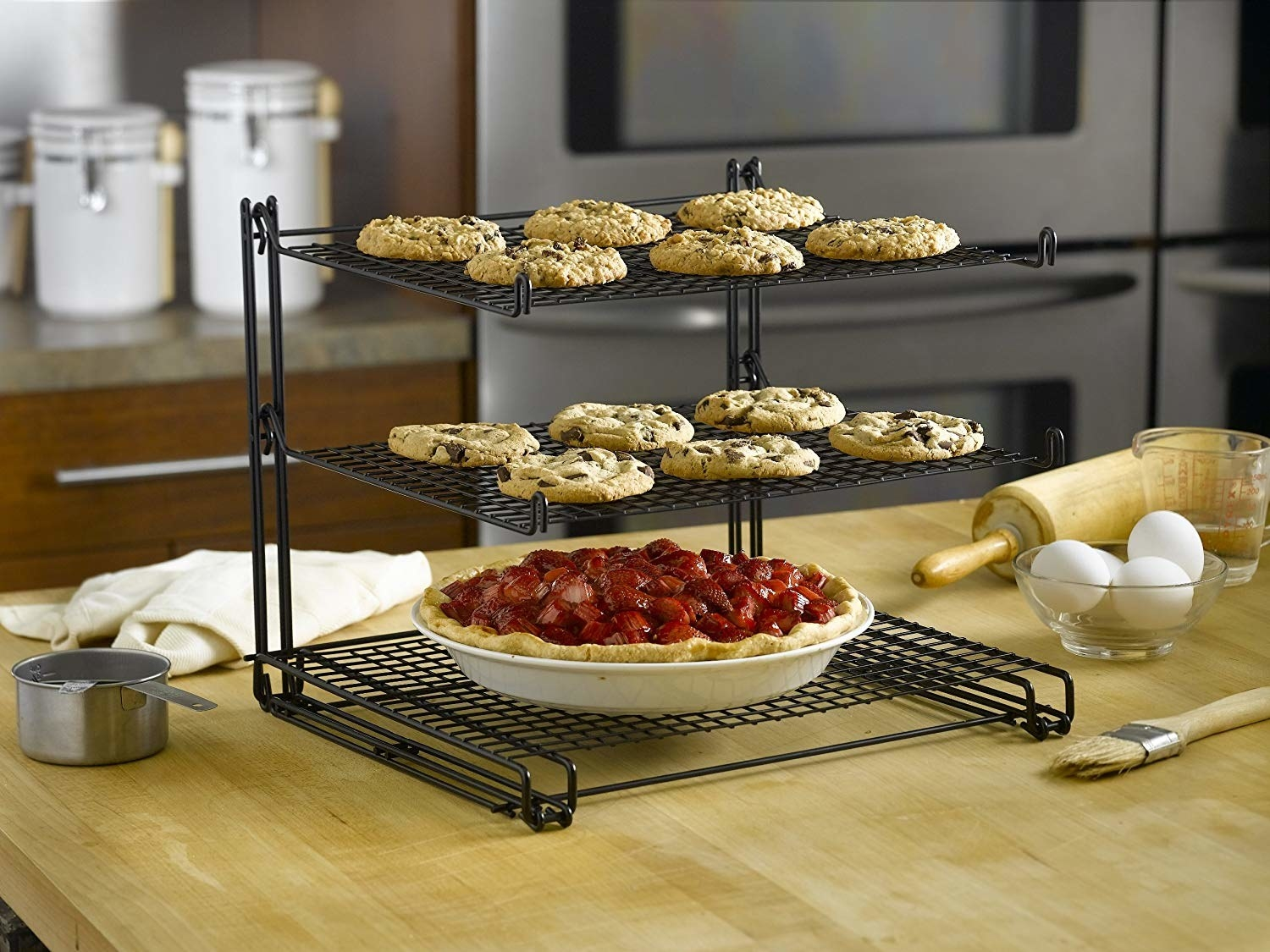 A black three tier cooling rack with baked goods cooling off on them