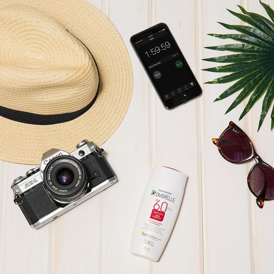 A bottle of sunscreen lying on a plain background with a camera, sunhat, phone, and pair of sunglasses nearby