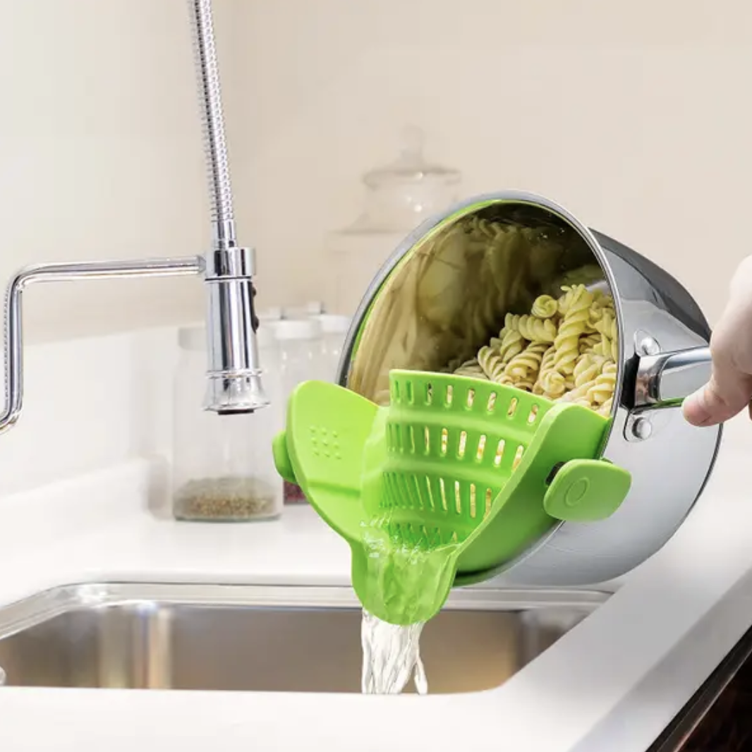 A model straining pasta from a green strainer clipped to the sides of the pot