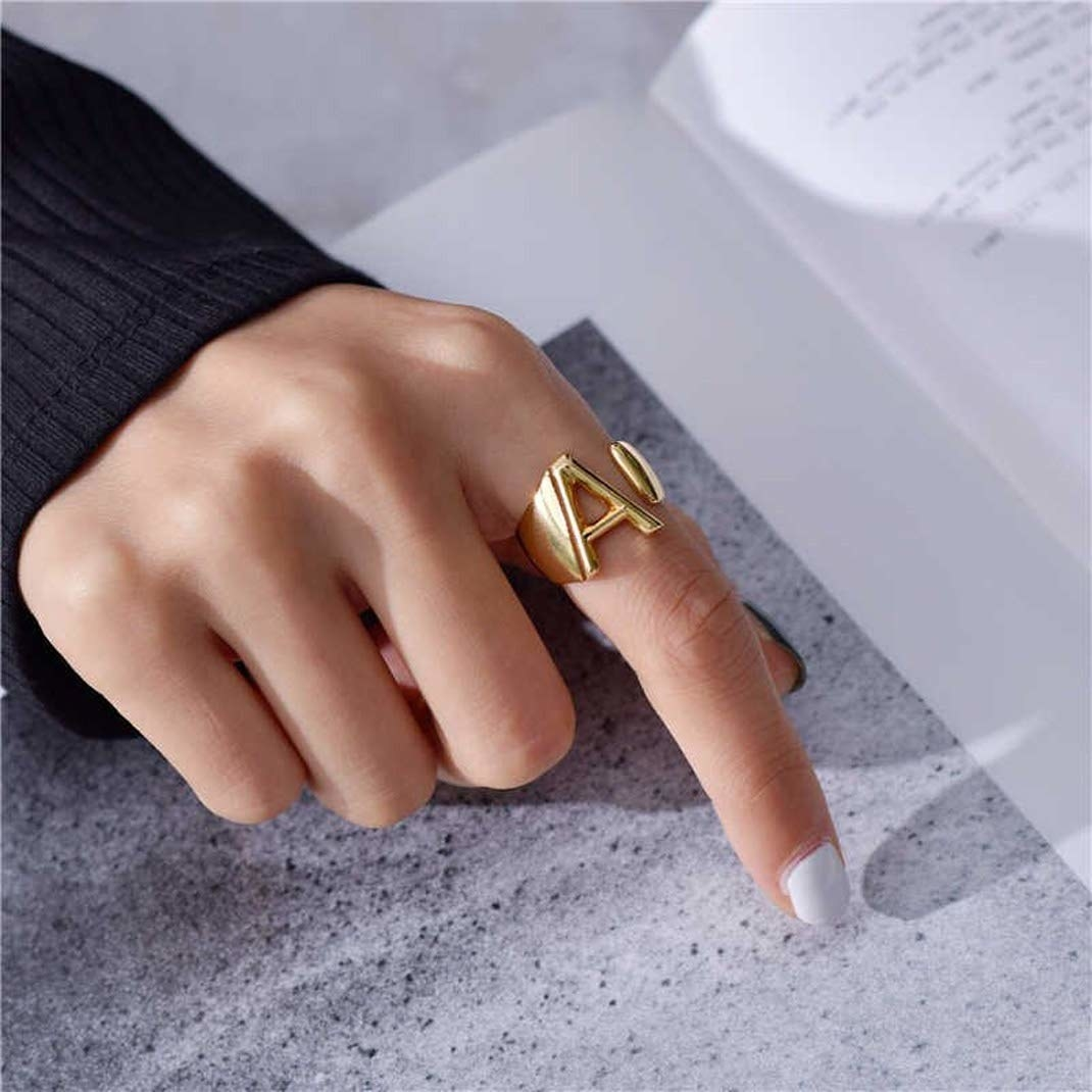 person wearing A initial ring