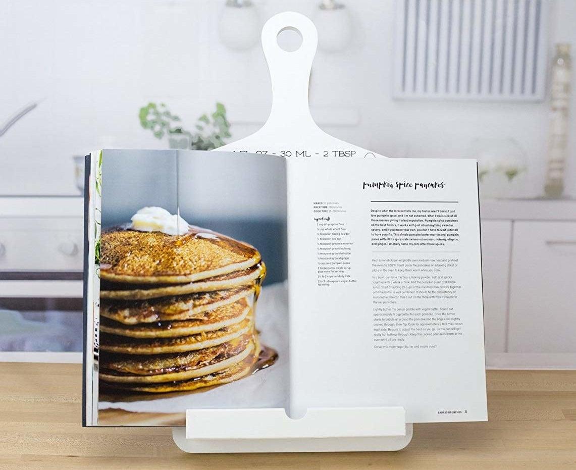 A large cookbook balanced on a wooden cookbook holder