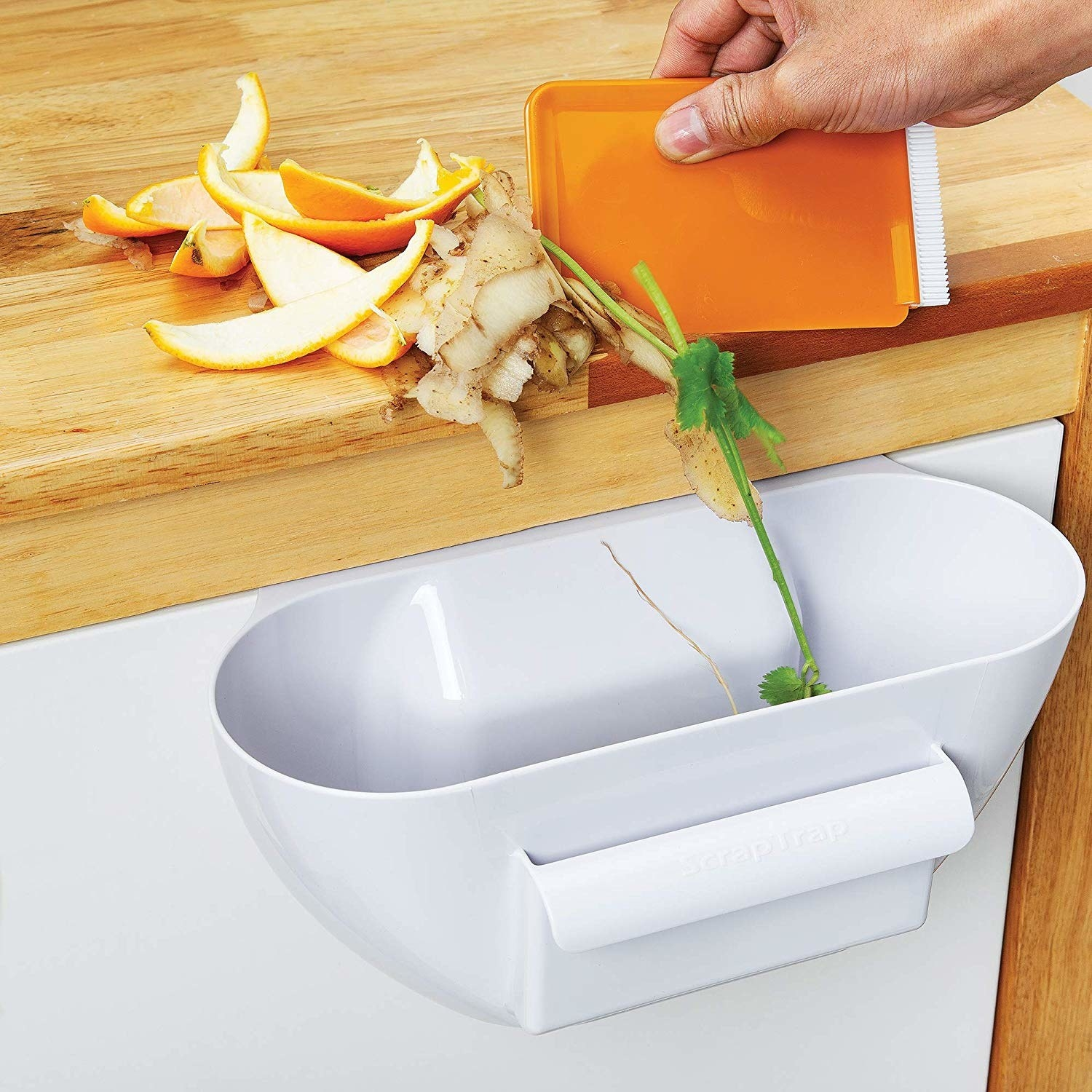 A person scraping vegetable and fruit peels into a small bin hanging off the end of a counter