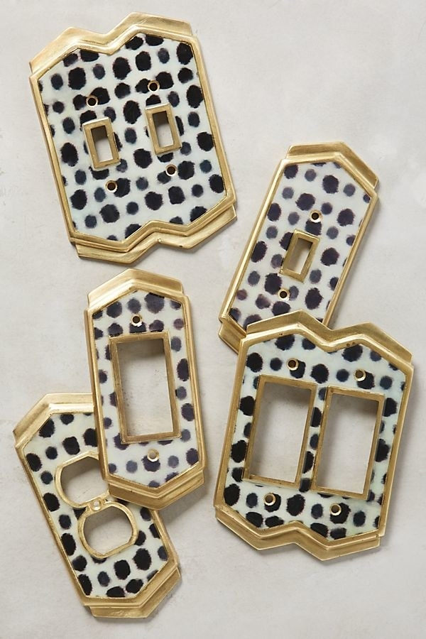 Different size switch plates lined in gold with black and white spots