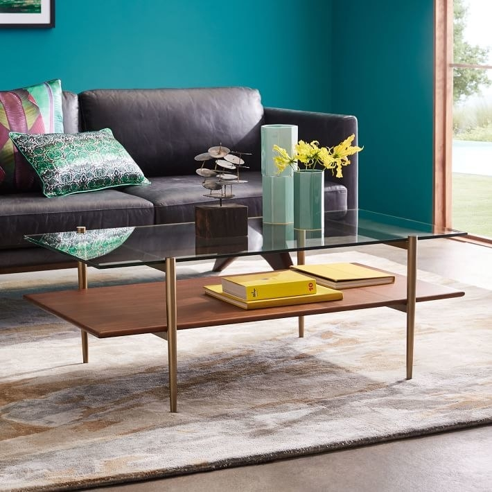 the coffee table with a glass top and wooden second layer