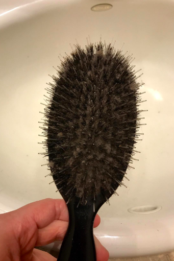 A reviewer's hairbrush caked with hair, so you can't even see the base holding the bristles