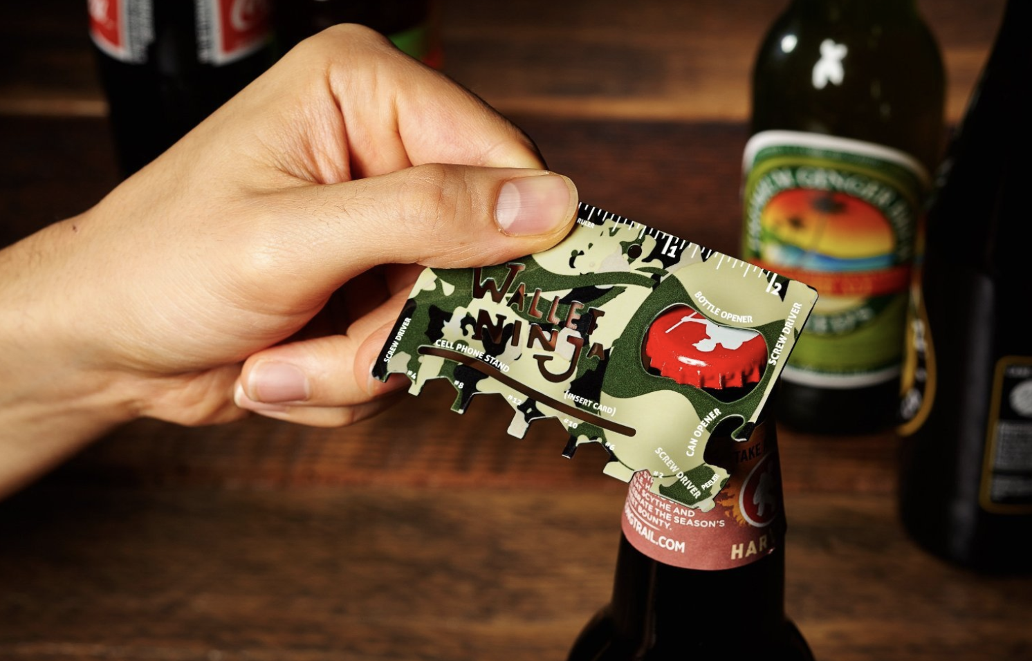 Hand uses camo print 18-in-1 multi-purpose pocket tool to open beer bottle