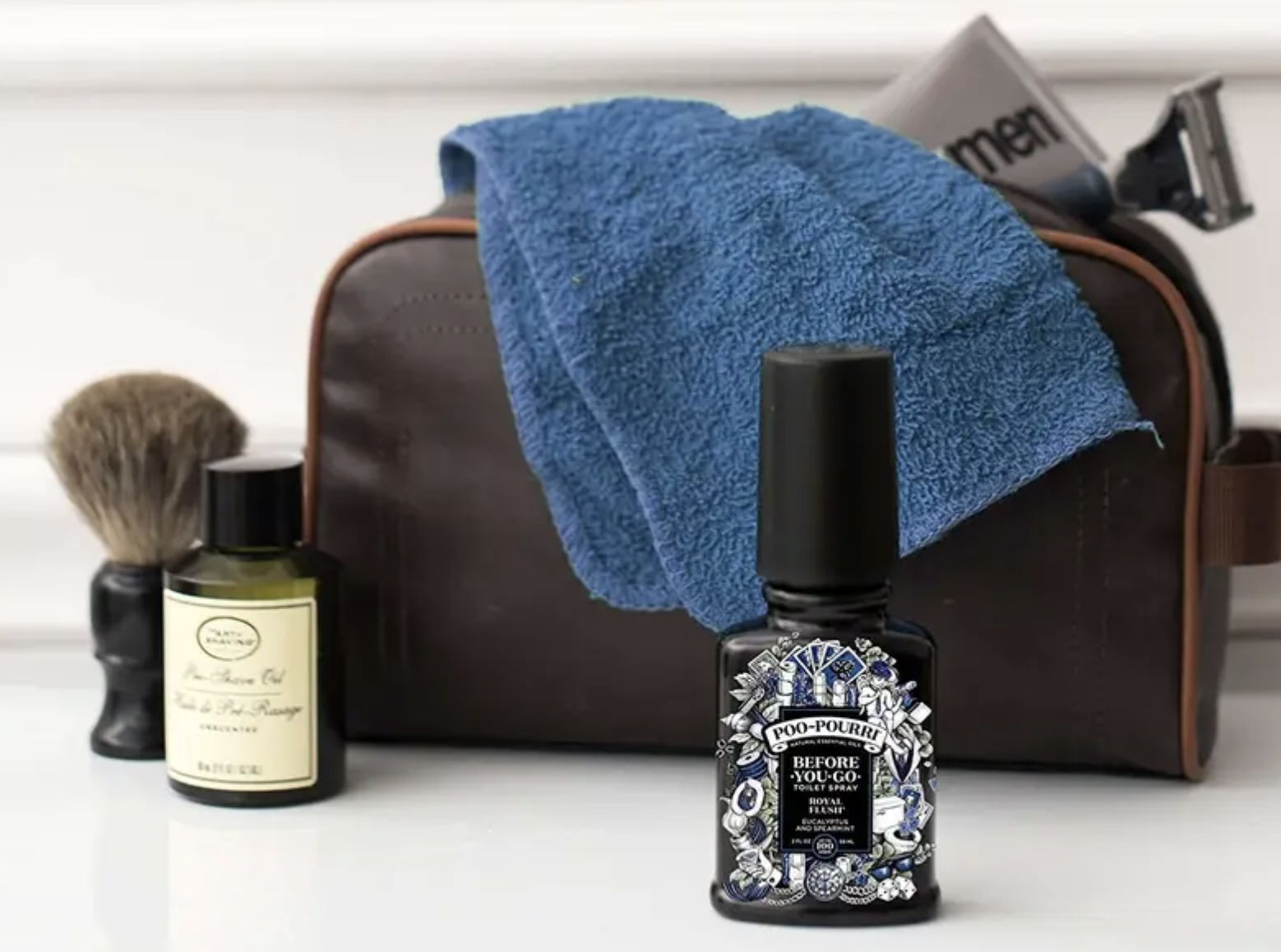 Bottle of black Poo-Pourri on a bathroom counter with a grooming kit