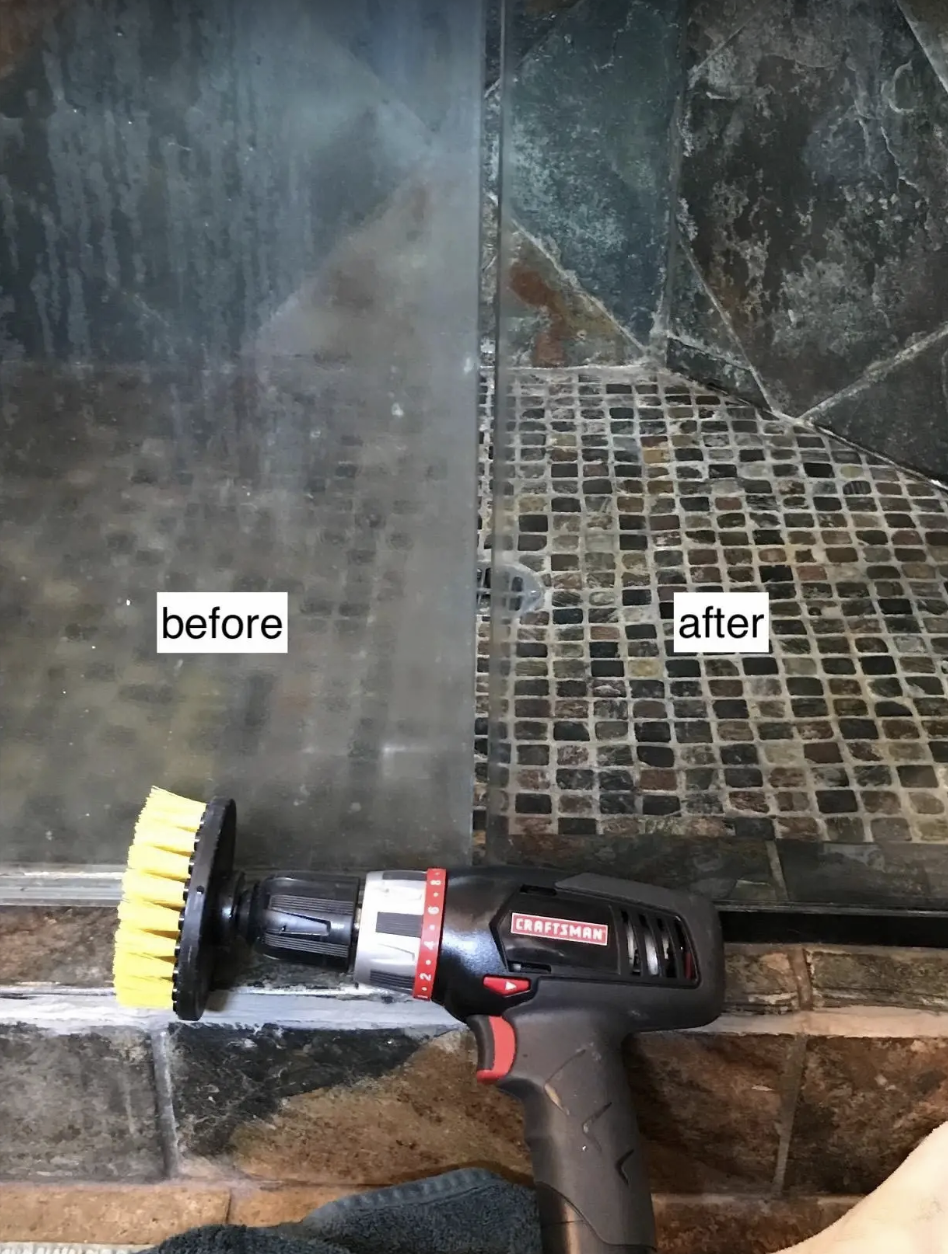 A reviewer's drill brush lays in front of two shower glass panels, one unclear and full of scum and the other so clear that it's hard to tell there's glass there