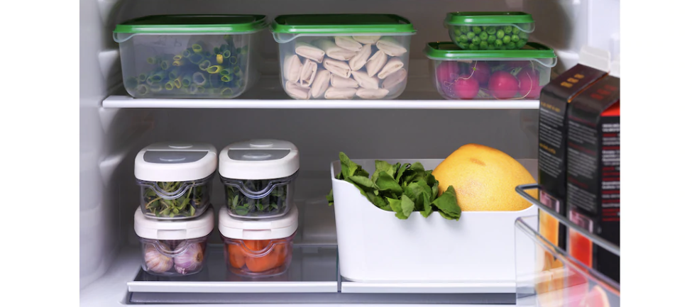 Multiple food containers with different items stored inside a fridge.