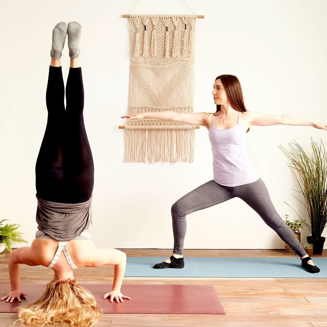 Two people doing yoga while wearing the socks