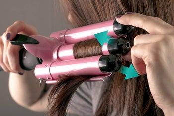 Model using the three-barrel curler on their hair