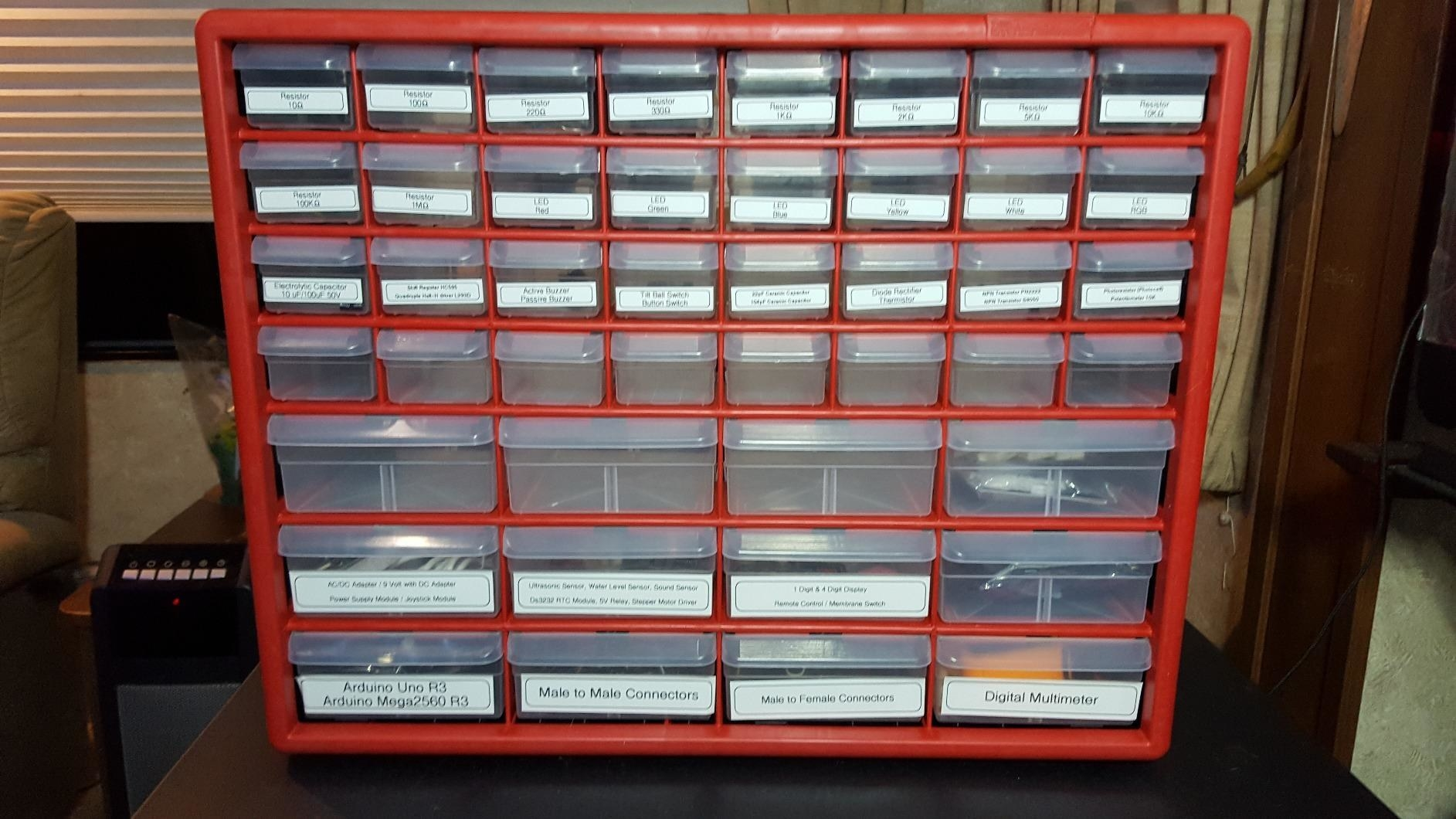 red cabinet with many tiny plastic drawers of various sizes