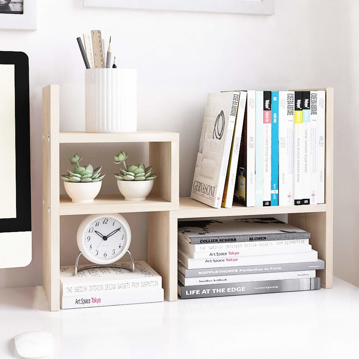 the light wood shelf set holding books, succulents, a clock, and a pencil cup