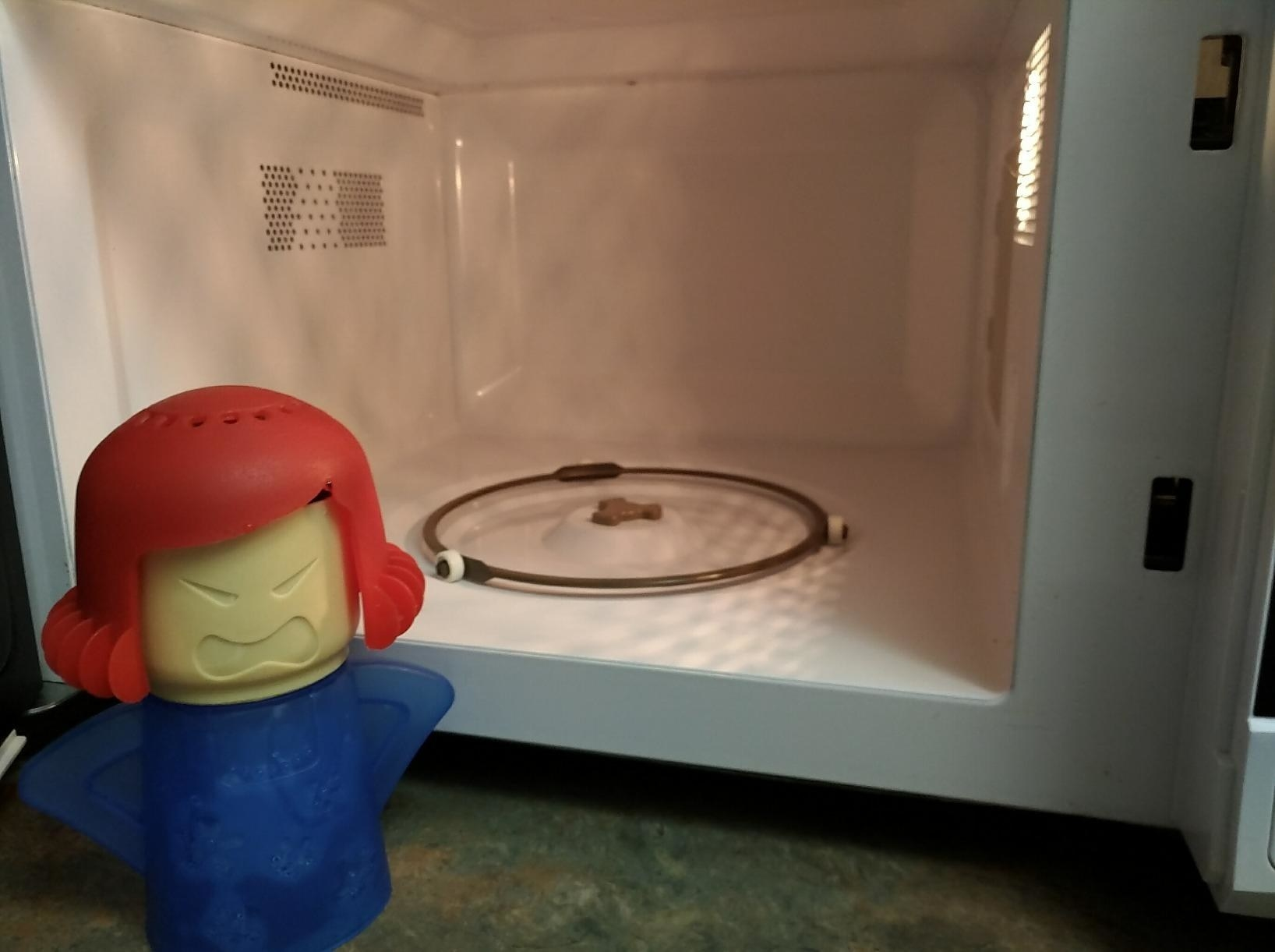 the person-shaped cleaner with vents at the top of its head next to a clean microwave