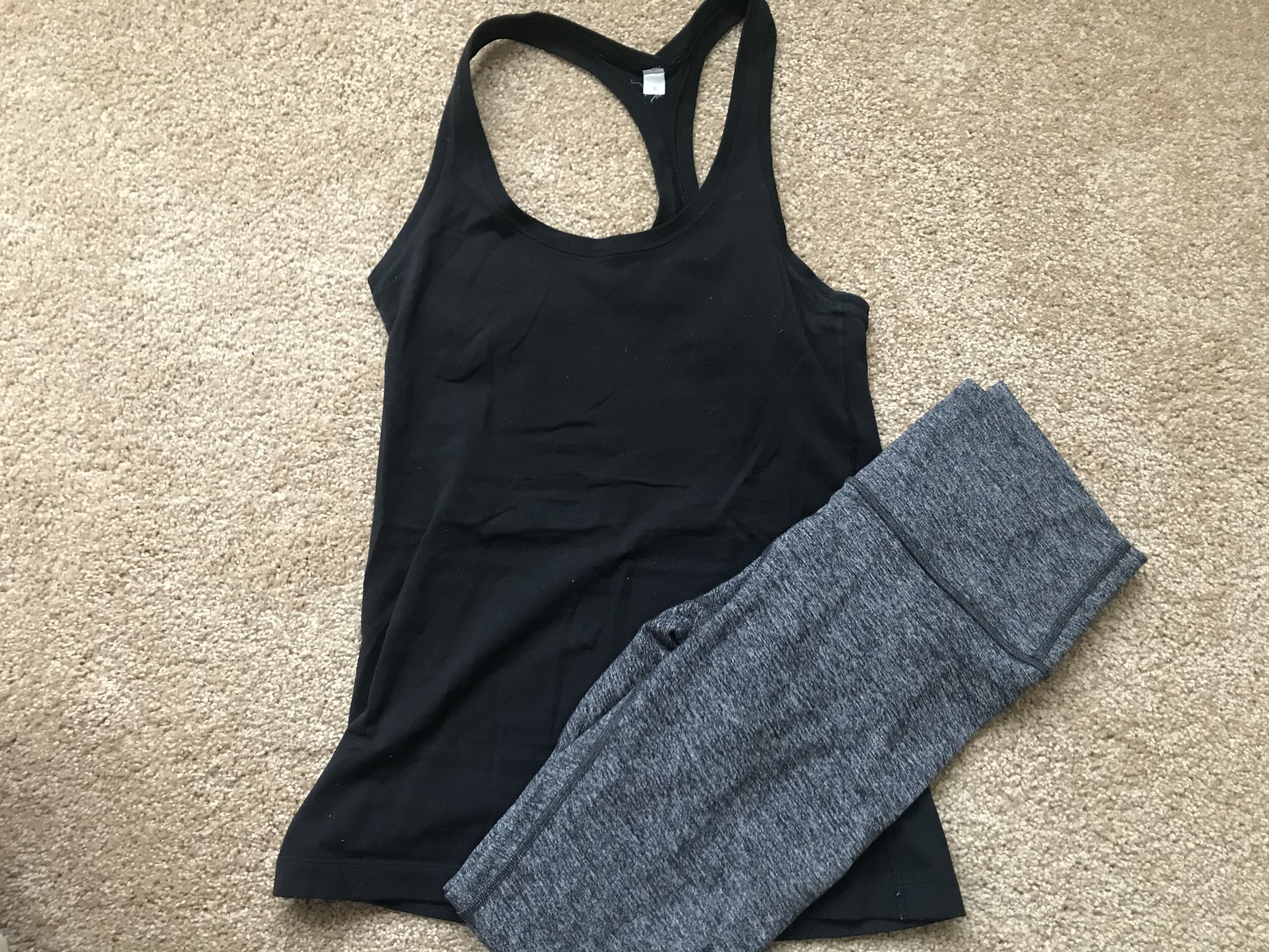 A workout top and leggings laid out on the floor