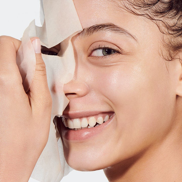 A model peeling off the opaque white sheet mask