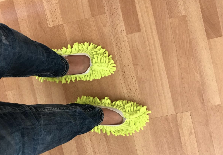 Reviewer wears yellow mop slippers to clean a hardwood floor