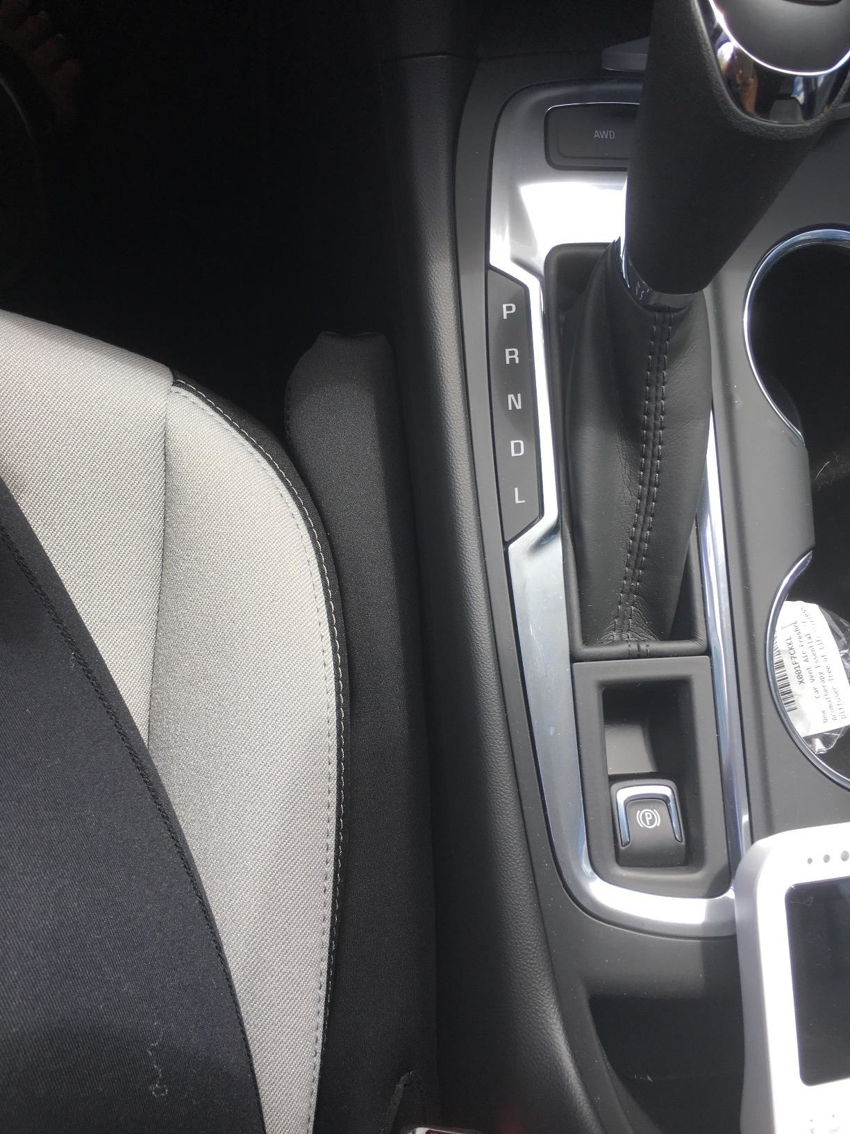 A small black seat filler wedged between the chair and console of a car