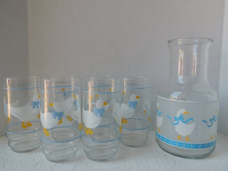 A collection of clear '80s glasses with geese with blue bows on it.