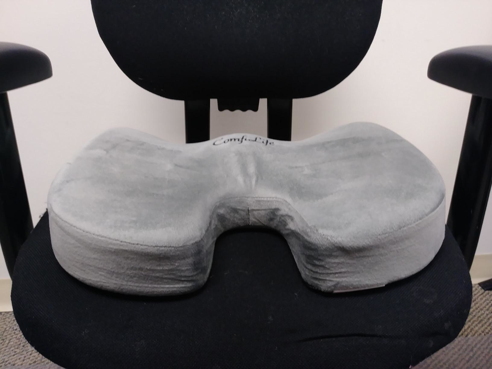 A gray memory foam seat cushion propped on an office chair