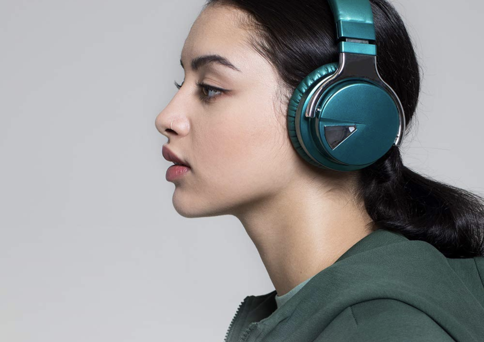 Model with a pair of dark teal over the ear headphones