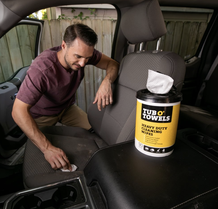 Model uses Tub O' Towels Heavy Duty cleaning wipe to get mud stains off a black car seat