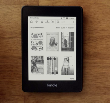A Kindle Paperwhite turned on to show the layout out six books on the menu screen