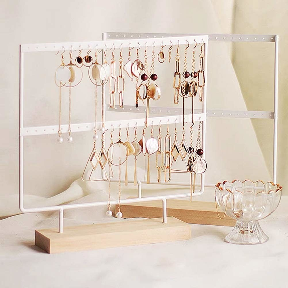 A white two-tiered display with earrings hanging from it