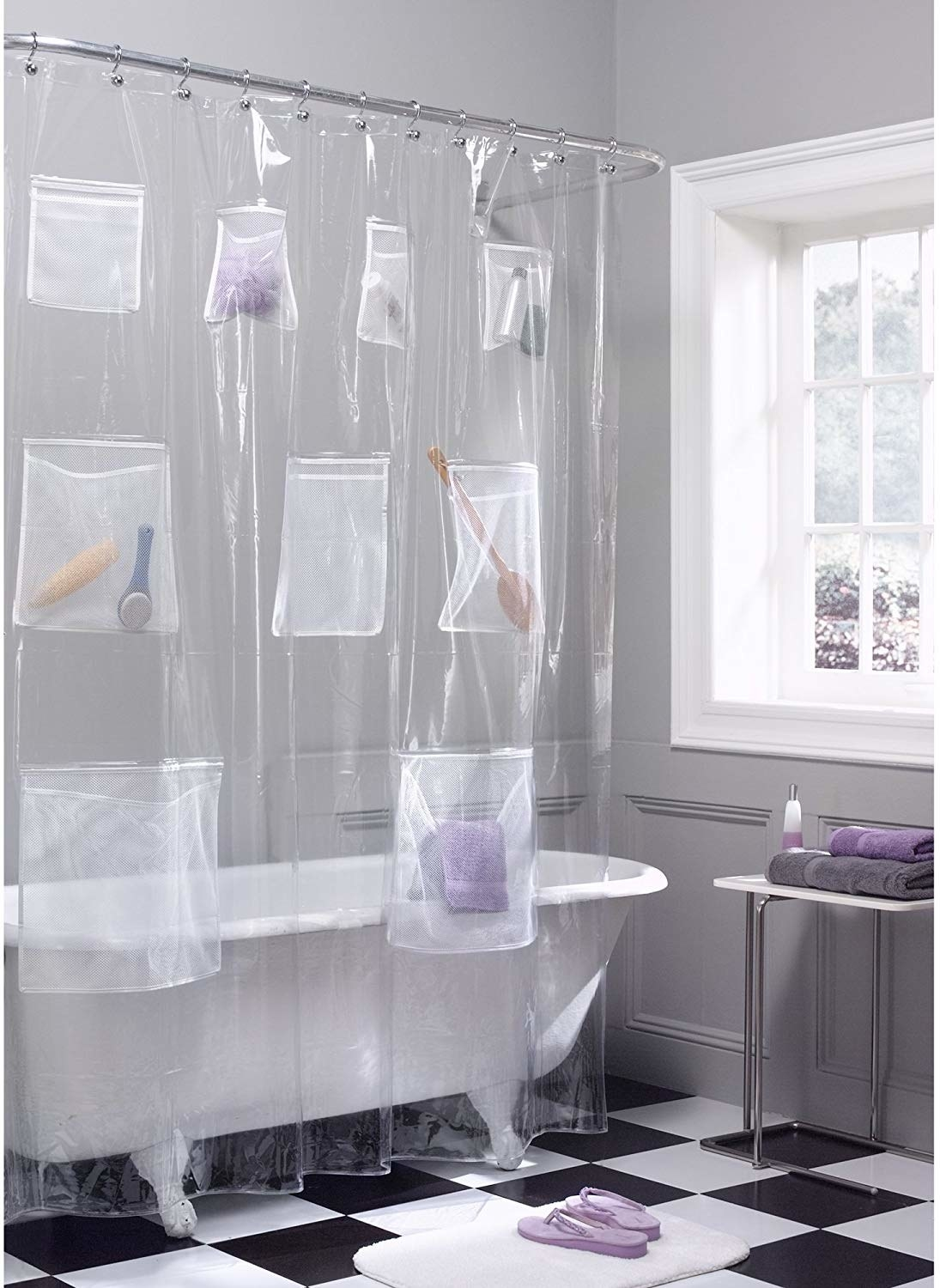 clear shower curtain with eight pockets of various sizes and items in them
