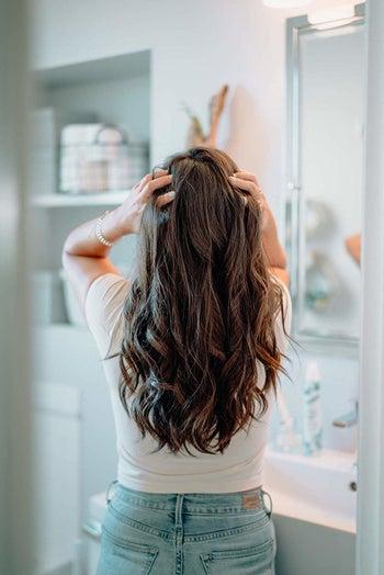 A model running her hands through her long, wavy hair